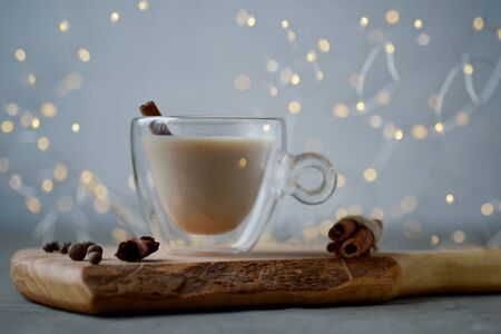 Masala warm spicy tea Indian chai. Warming drink with spice healthy food, conception health. New year, Christmas decoration, festoon shining, glowing garland, winter holidays, treat ingredients components
