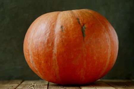 big orange pumpkin on boards raw fresh decorative ribbed vegetable on wooden brown table dark background copy space seasonal autumn still life healthy organic nutritious food conception