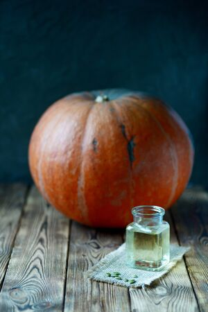 Yellow pumpkin oil in glass transparent opened jar in front of big orange pumpkin raw vegetable seeds and bottle on wooden brown table dark background autumn still life healthy organic nutritious food Stockfoto