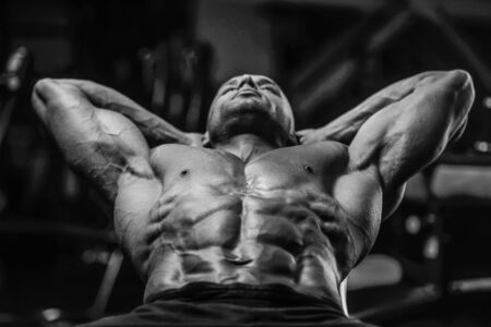 Handsome strong athletic men pumping up muscles workout fitness and bodybuilding concept background - muscular bodybuilder fitness man doing abs exercises in gym naked torso