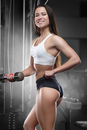 Fitness woman pumping up muscles biceps and triceps workout fitness and bodybuilding concept. Pretty caucasian girl in the gym background arms exercises in gym naked torso Stock Photo