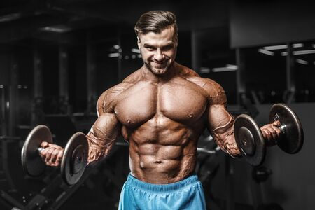 Bodybuilder handsome strong athletic rough man pumping up biceps muscles workout fitness and bodybuilding healthy concept background - muscular fitness men doing arms exercises in gym naked torso Banque d'images