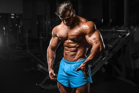 Bodybuilder handsome strong athletic rough man pumping up abs muscles workout fitness and bodybuilding healthy concept background - muscular fitness men doing abdominal exercises in gym torso