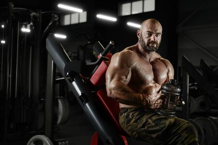 Bodybuilder strong athletic rough man drinking water after workout workout fitness and bodybuilding healthy concept background - muscular fitness men doing exercises in gym naked torso Stock Photo