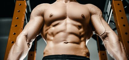Bodybuilder handsome strong athletic rough man pumping up abs muscles workout fitness and bodybuilding healthy concept background - muscular fitness men doing abdominal exercises in gym naked torso