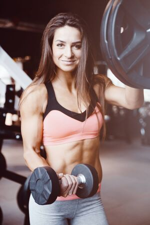 Fitness woman pumping up muscles workout. Pretty caucasian fitness girl and bodybuilding concept gym background abs, arms, back, chest exercises in gym naked torso Stock Photo