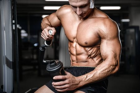 Bodybuilder strong athletic rough man with protein powder after workout workout fitness and bodybuilding healthy concept background - muscular fitness men doing exercises in gym naked torso Stock Photo