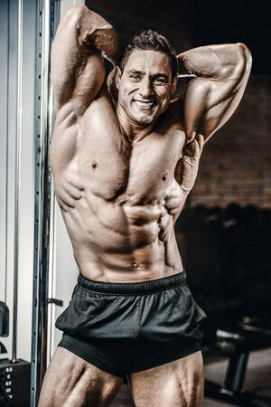 Bodybuilder handsome strong athletic rough man pumping up abs muscles workout fitness and bodybuilding healthy concept background - muscular fitness men doing abdominal exercises in gym torso Foto de archivo