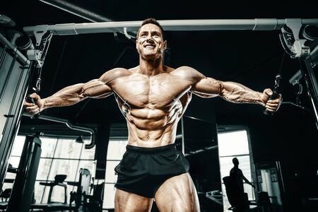 Muscular bodybuilder at cable crossovers fitness men pumping up muscles. Workout fitness exercises and bodybuilding concept background - Handsome athletic men doing bars exercises in gym naked torso