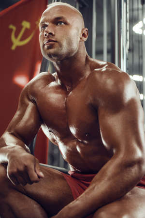 Bodybuilder handsome strong athletic man pumping up muscles. Workout fitness and bodybuilding healthy concept background - muscular fitness man doing exercises in gym with soviet flag