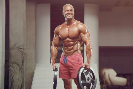 Bodybuilder handsome strong athletic rough man pumping up muscles workout fitness and bodybuilding healthy concept background - muscular fitness men doing arms exercises in gym naked torso