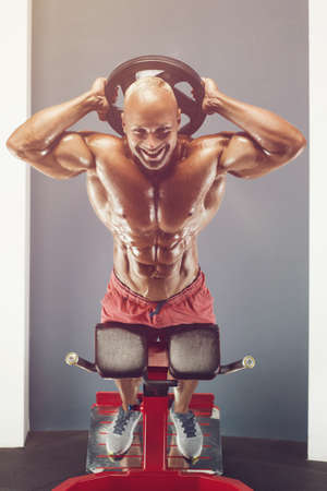 Bodybuilder handsome strong athletic rough man pumping up torso muscles hyperextension workout fitness and bodybuilding healthy concept background - muscular fitness men doing arms exercises in gym 版權商用圖片