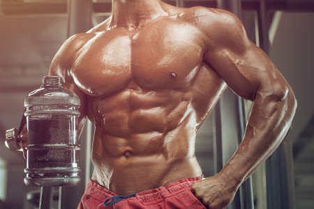 Bodybuilder strong athletic rough man drinking water after workout workout fitness and bodybuilding healthy concept design - muscular fitness men doing exercises in gym naked torso 版權商用圖片