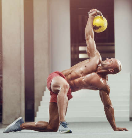 Bodybuilder handsome strong athletic rough man pumping up muscles with kettlebell workout fitness and bodybuilding healthy concept background - muscular fitness men doing chest exercises in gym