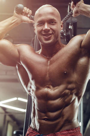 Bodybuilder handsome strong athletic rough man pumping up triceps muscles workout fitness and bodybuilding healthy design concept - muscular fitness men doing arms exercises in gym naked torso
