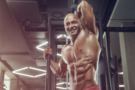 Bodybuilder handsome strong athletic rough man pumping up abs muscles workout fitness and bodybuilding healthy concept design - muscular fitness men doing abdominal exercises in gym naked torso