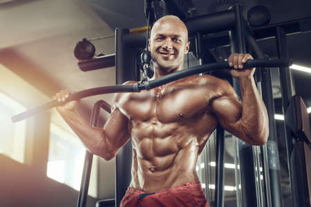 Muscular bodybuilder fitness man doing pull-ups exercises in gym naked torso. Handsome strong athletic men pumping up back muscles workout fitness and bodybuilding concept background