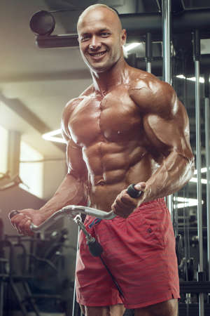 Bodybuilder handsome strong athletic rough man pumping up muscles biceps workout fitness and bodybuilding healthy concept background - muscular fitness men doing arms exercises in gym naked torso