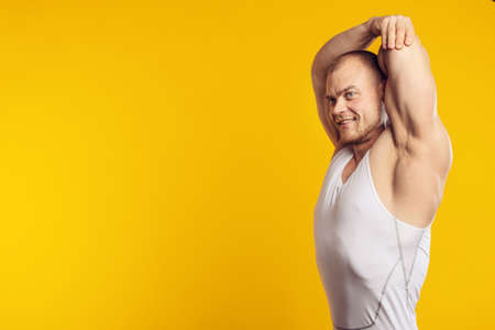 Studio Closeup portrait of muscular man in white shirt, standing over isolated yellow background. Fitness, bodybuilding and work out concept