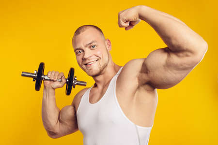 Studio portrait of muscular man with dumbbell in white shirt, standing over isolated yellow background. Fitness, bodybuilding and work out concept