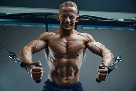 Bodybuilder handsome strong athletic good looking man pumping up chest muscles workout fitness and bodybuilding healthy concept - muscular fitness men doing pectorals exercises in gym naked torso
