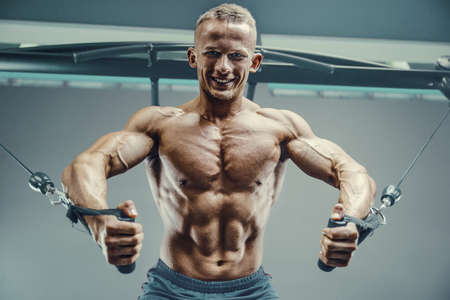 Bodybuilder handsome strong athletic good looking man pumping up chest muscles workout fitness and bodybuilding healthy concept - muscular fitness men doing pectorals exercises in gym torso