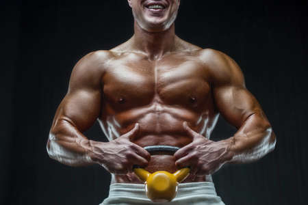 fit man training training abs muscles at gym. Pumping up abdominal exercise. Close up muscles at workout. Bodybuilding, fitness and health care concept.