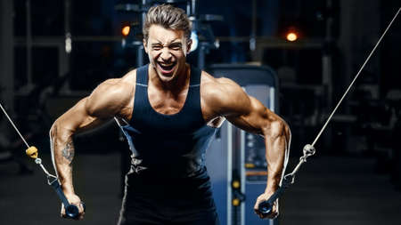 fit man doing cable crossover. Training pectoral muscles at gym. Pumping up chest exercise. Close up muscles at workout. Bodybuilding, fitness and health care concept.