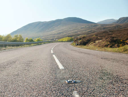 road ahead: country road winding through the Scottish Highlands. UK.  Focus on the reflector dividing line. Stock Photo