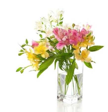 Csokor virágot Alstroemeria átlátszó vázában elszigetelt fehér háttérrel.