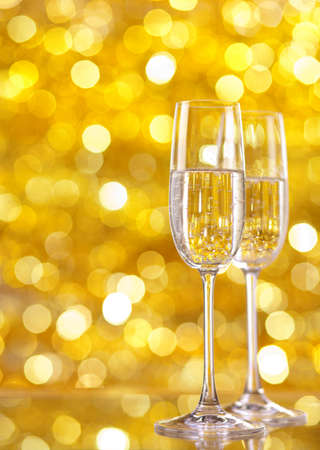 Two glasses of champagne with lights in the background. very shallow depth of field, focus on near glass. Stock Photo