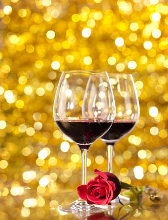 red rose bokeh: Two glasses of red wine with lights in the background. very shallow depth of field, focus on near glass and rose Stock Photo