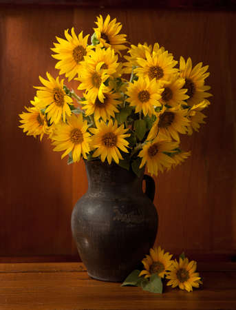 Still life. Beautiful Sunflowers in  old clay pot against a wooden wall