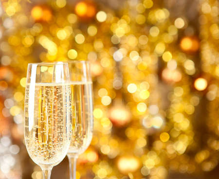 champagne flute: Two glasses of champagne with lights in the background  very shallow depth of field, focus on near glass  Stock Photo