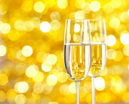 champagne flutes: Two glasses of champagne with lights in the background. very shallow depth of field, focus on near glass. Stock Photo
