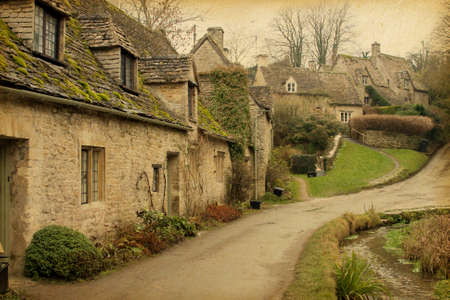 english countryside: Bibury Traditional Cotswold cottages in England, UK  Photo in retro style  Paper texture  Stock Photo