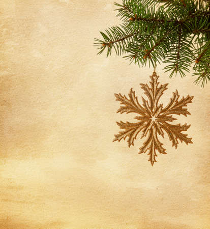 Christmas golden snowflake hanging on a spruce on paper  background photo