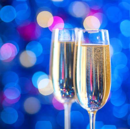 sektglas: Zwei Gläser Champagner mit Lichtern im Hintergrund. sehr geringe Schärfentiefe, auf nahe Glas konzentrieren.