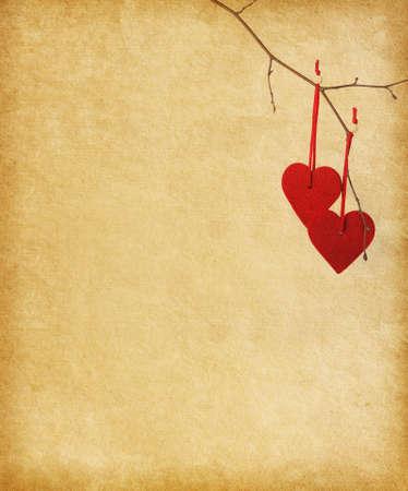 Két piros szív, lóg egy ágon át a papír háttér.