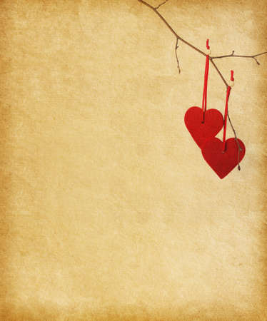 two red heart, hanging on a branch over the paper background.