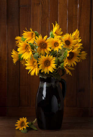 Still life  Bunch of Beautiful Sunflowers  against a wooden wall photo