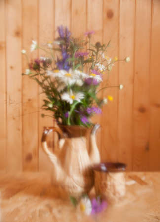 tarnished: Bouquet of wild flowers on the background of a wooden wall. Still life  is photographed through  tarnished glass. Selective focus.