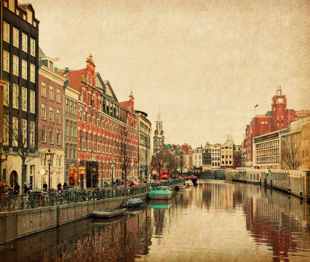The Singel is one of the numerous canals in Amsterdam, Netherlands   In the background Munttoren   Photo in retro style  Paper texture  photo