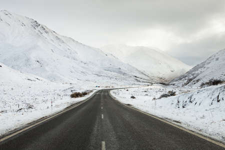 Empty mountain road on a cloudy winter day   South Island, New Zealand photo