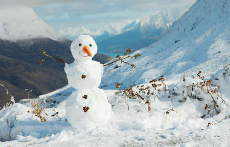 Happy snowman in mountains