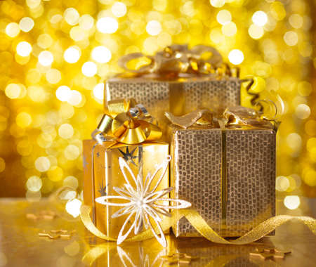 Gold Christmas gifts on background of defocused golden lights  photo