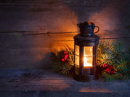 new year s eve: Cristmas lantern  in night on old wooden background  focus on the wick candles Stock Photo