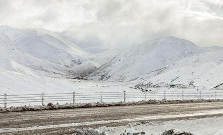 Mountain road on a cloudy winter day after snowfall  South Island, New Zealand photo