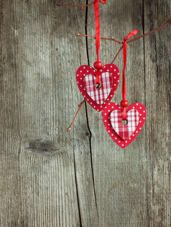 two red hearts, hanging on a branch over the old wooden background  photo