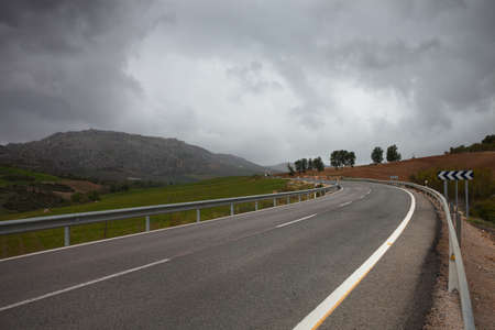 guardrails: a winding  road through hills  Andalusia, Spain  Stock Photo